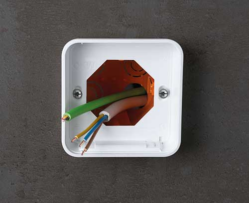 Partie inférieure du boitier vissée sur la boîte d'interrupteur